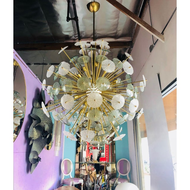 Italian Sputnik chandelier shown in clear and smoky green molded Murano glass with bubbles on unlacquered brass frame. The...