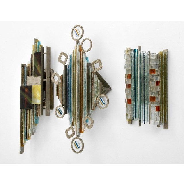 Unique set of three sconces in graduated sizes made of segmented art glass bars on a steel frame. Designed by Albano Poli...