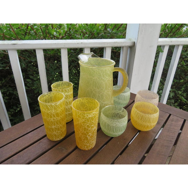 This is a beautiful set of vintage glass. It is a mid-century drink pitcher with 7 matching tumblers in a spaghetti string...