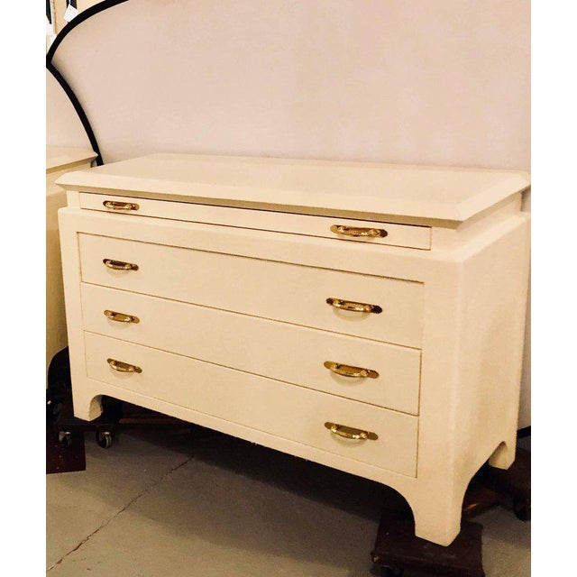 A pair of custom quality commodes, chests or nightstands each linen wrapped. These palatial chests are fashioned in the...