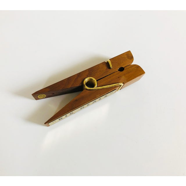 "A mid century walnut note clip in the shape of a clothes pin. A brass plaque on one side reads ""Big Deals"" with a small..."