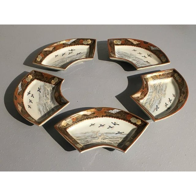A beautifully decorated set of five Kutani porcelain fan shaped dishes, featuring a design of finely painted plovers...