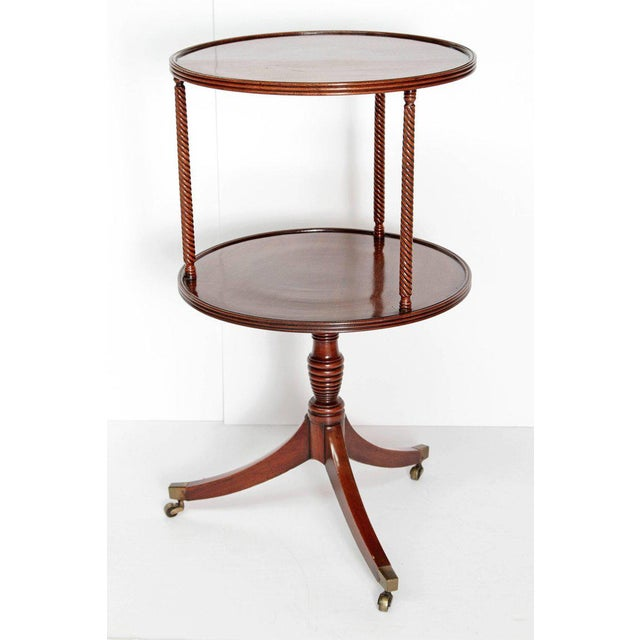 An English George III two tiered dessert table of mahogany on tripod swivel base. Ringed detail on tier edges, twisted...