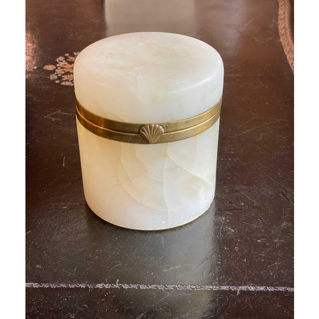 A light cream colored Italian marble with a hinged top and brass rim.