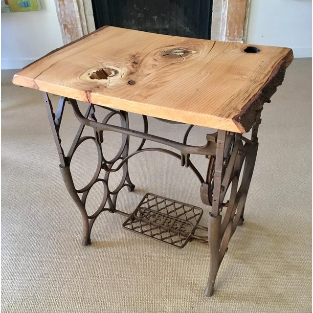 For lovers of nature and eclectic styles, this cherry raw edge table married with an ornate antique iron sewing machine...
