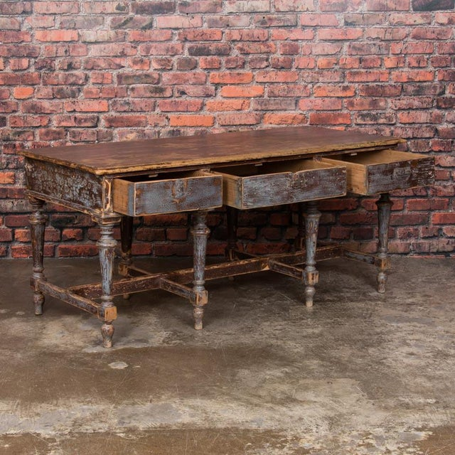 Old layers of distressed blue/gray and deep brown/rust colored paint create an attractive mix in this unique work table....