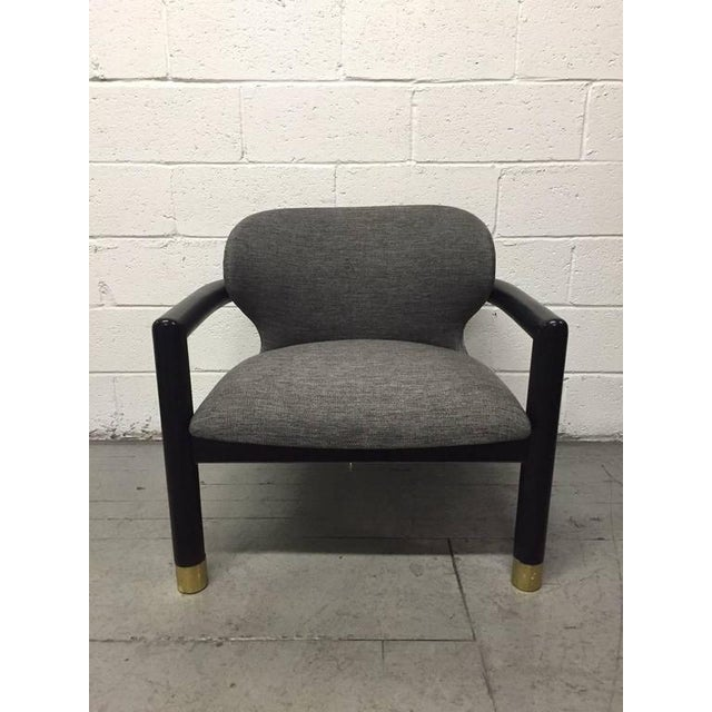 Pair of sculptural lounge chairs. Has brass sabots. Chairs are newly upholstered in gray wool-blend with a black painted...