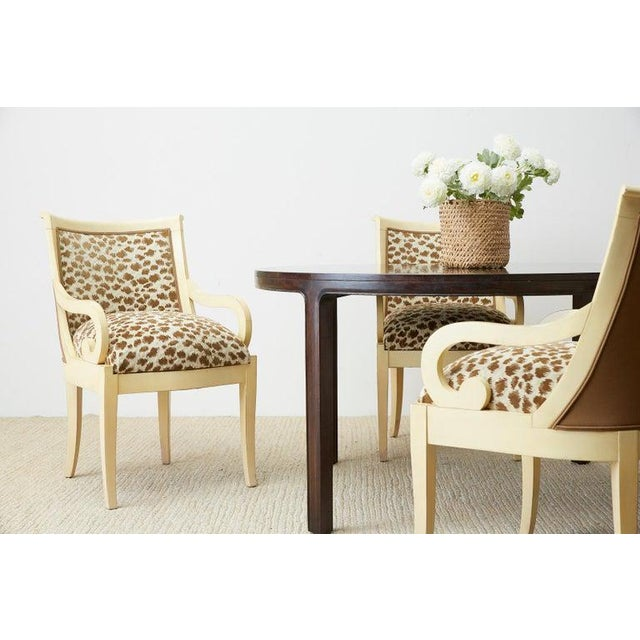 Bespoke set of four lacquered dining chairs or armchairs made in the regency taste. Featuring large scrolled arms and...
