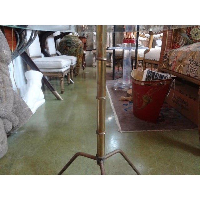 Charming Italian Gio Ponti inspired Mid-Century Modern patinated brass tripod table with glass top. This table is the...