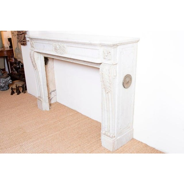 Exquisitely carved French Louis XVI style fireplace mantel in carrara marble with nice original patination. The frieze is...