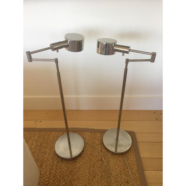 Two Phoenix Day telescoping swing arm floor lamps with round shades and bases in polished nickel. Adjustable height and...