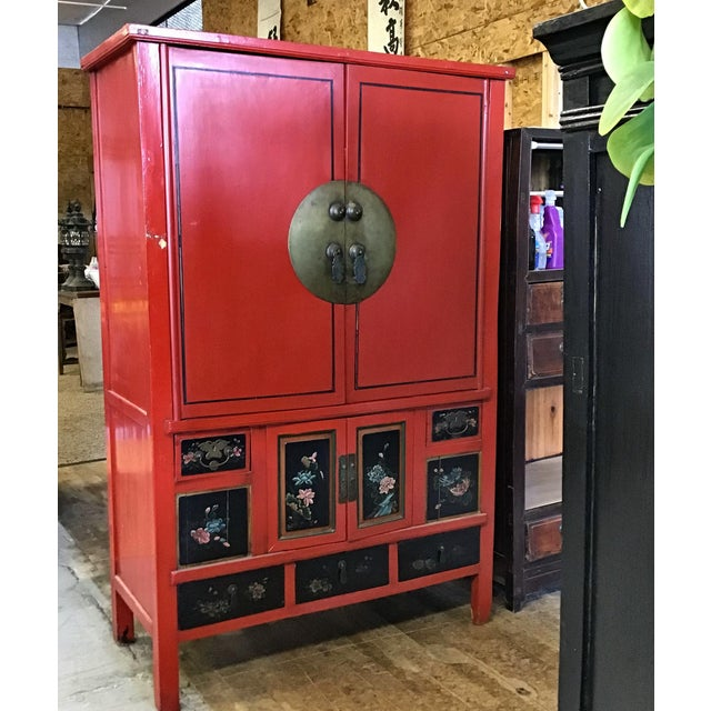 Gorgeous red and black armoire with brass hardware from the 1900s, China. This Chinese armoire is made of red and black...