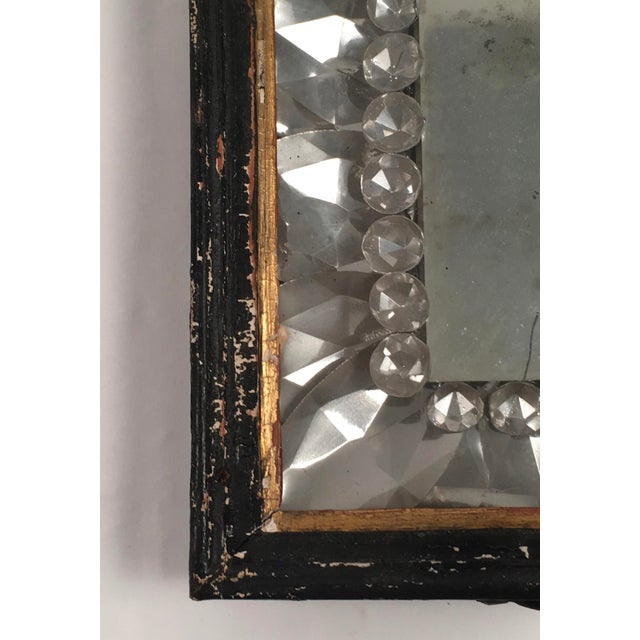 A striking, early American mirrored wall sconce, the ebonized wood frame, with gilded interior fillet, surrounding a...