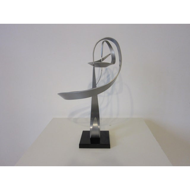 A kinetic bent aluminum three piece sculpture mounted on a black Lucite base with ink stamp signature to the bottom . The...