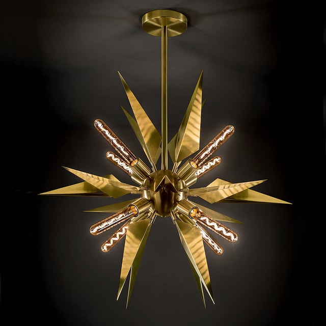 A brushed brass starburst light created from a central globe whih supports LED filament lamps. Price includes lamps....