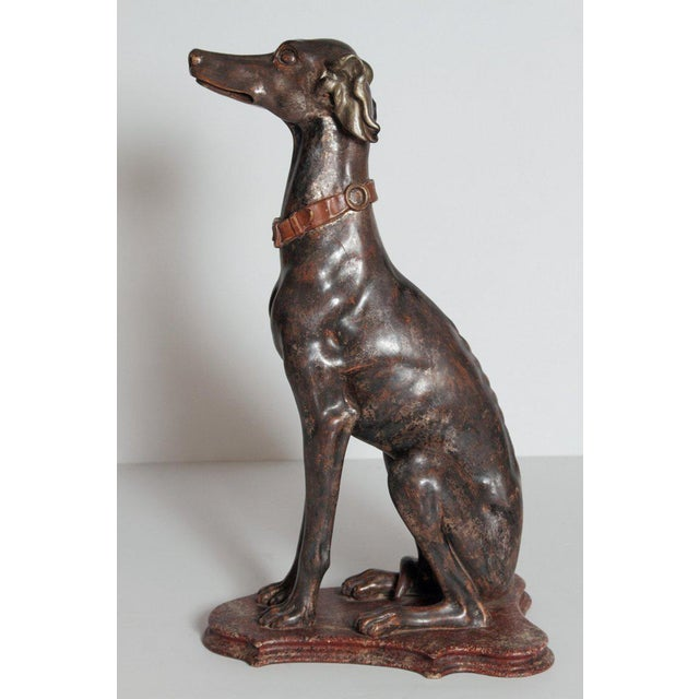 A fine example of a tall Italian greyhound sculpture from the 19th century. The greyhound is sitting attentively on a...
