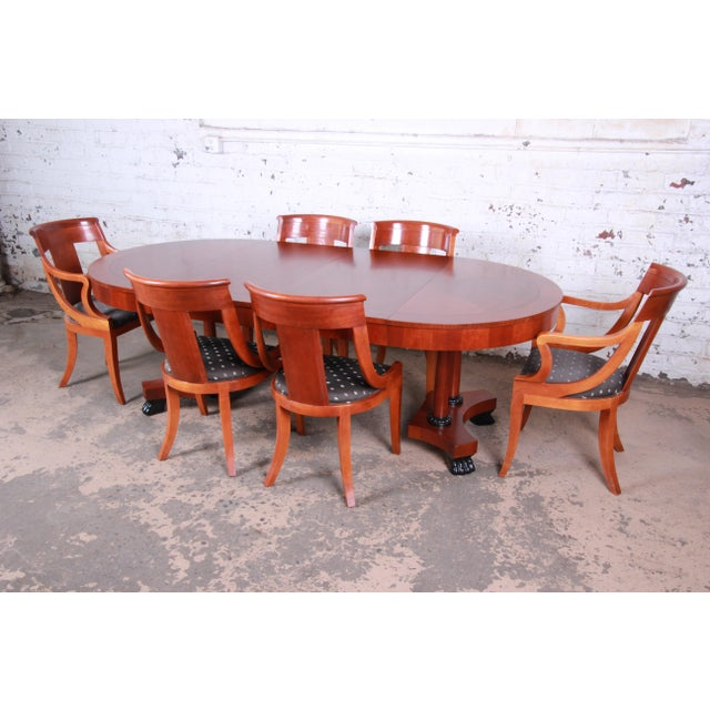 An outstanding Neoclassical style extension dining table and chairs from the Palladian Collection by Baker Furniture....