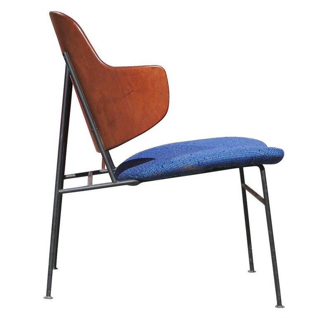 Penguin lounge chair designed by Ib Kofod-Larsen with molded birch plywood back, black iron base, and blue upholstered...
