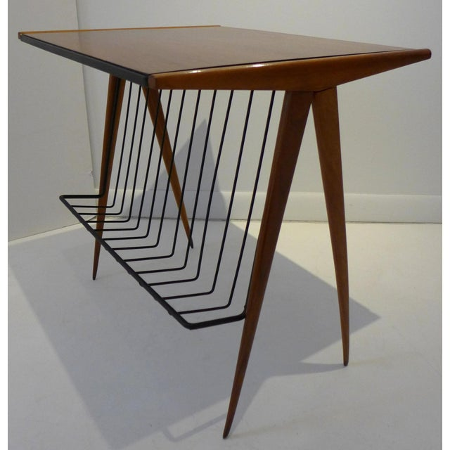 A seldom-seen Mid-Century magazine table in walnut by Arthur Umanoff. The wrought iron magazine holder extends into a...