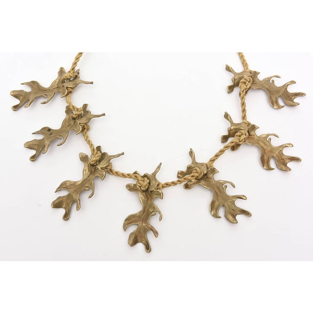 This organic modern necklace by Mary McFadden has beautiful gold silk metallic braided rope that houses the 6 bronze...