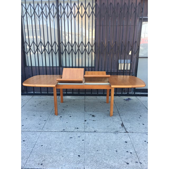 Danish teak table with sculpted teak legs and two butterfly leafs by Diethelm Scanstyle. This mid-century modern style...
