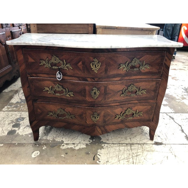 18th century French Louis XV period marquetry Inlayed commode. Retaining a contemporary shaped white marble top, over the...