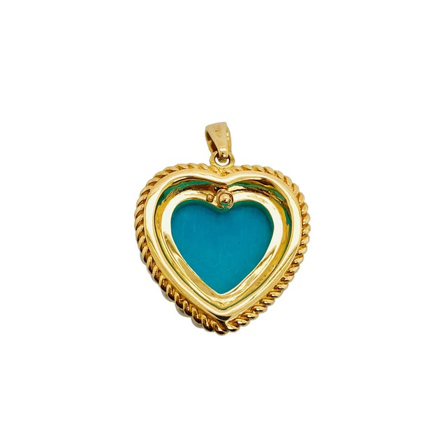 A fine vintage 14K yellow gold with a Persian turquoise heart surrounded by cultured seed pearls. The Heart has a rope...