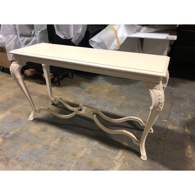 Large off-white George console table, with curvilinear legs and stretchers. Carved floral motif on legs and stretchers,...