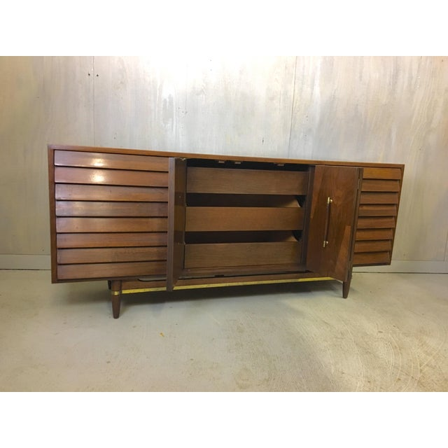 This well-constructed walnut piece from the Dania Line designed by Merton Gershun for American of Martinsville features...