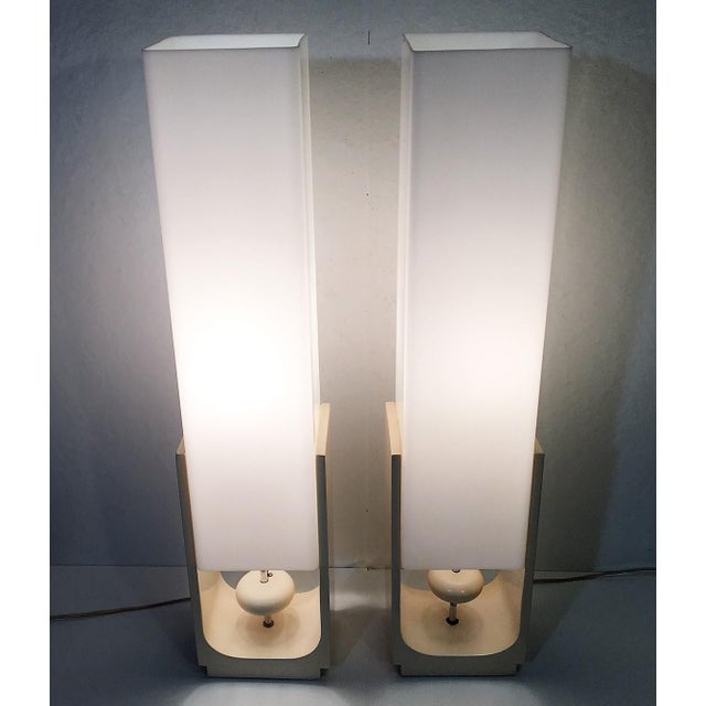 Offered is an extraordinary pair of white acrylic mid-century era square tube table lamps. Each has a lacquered wood base...