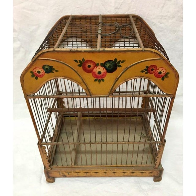 Floral accents on an ochre background frame this antique birdcage. A pleasing shape and scale with hand formed wire. A...