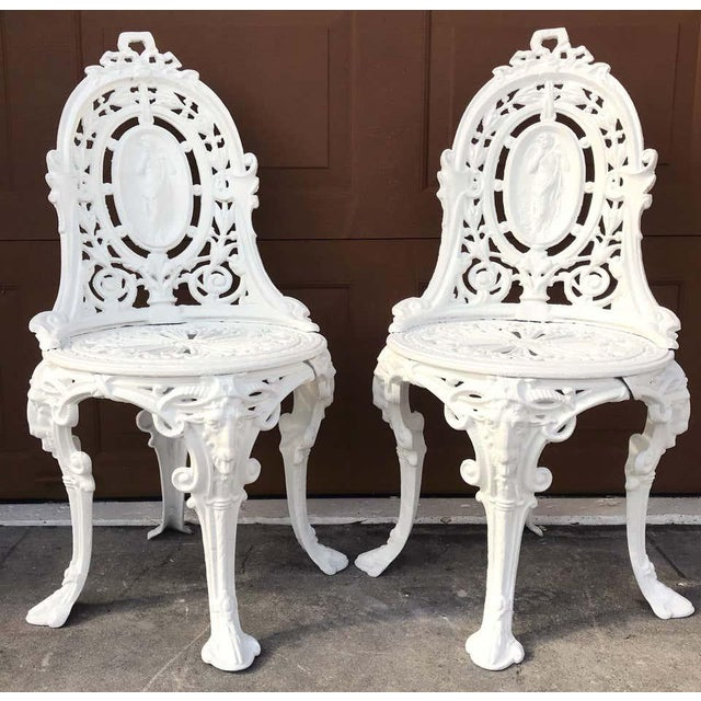 Pair of Victorian Angel motif wrought iron garden chairs, restored Each one with oval ribbon pierced back rests, with...