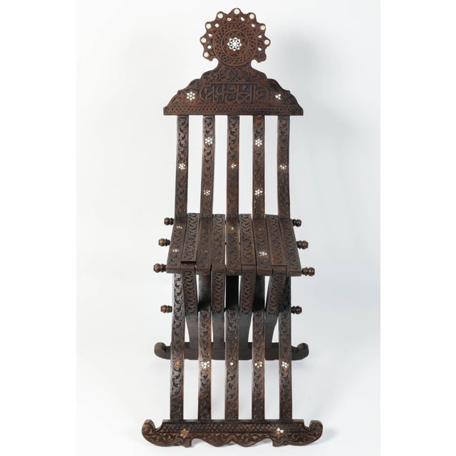 Middle Eastern Syrian wooden folding chair with intricate foliate carving and mother-of-pearl inlays. Inlaid with mother-...