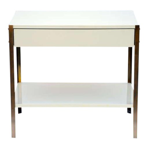 Pair of Minimalist ivory lacquer and brass nightstands. Bottom shelf height: 6.5 in. tall. Soft close drawer glides. Also...