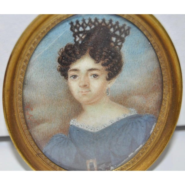 Mid 19th Century English School Miniature Portrait of a Lady in a Blue Dress This charming young woman has powder white...