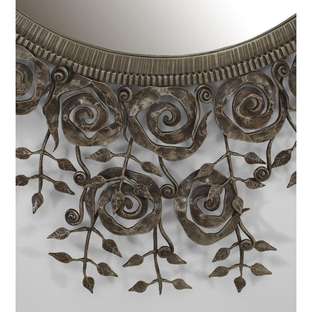 French Art Deco style wrought iron wall mirror with a filigree floral and scroll border on 2 sides of a centered round mirror