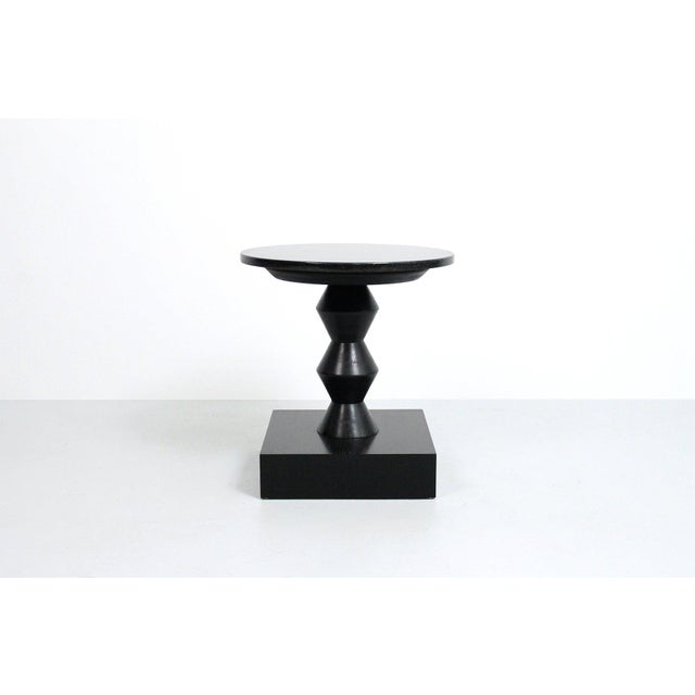 Rare Peter Shire Post Modern side/lamp table with black cerused wooden base and circular granite top. This example comes...