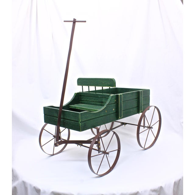 Handmade vintage wagon planter. Details include painted and distressed green slatted boards, wire spokes and metal wheels....