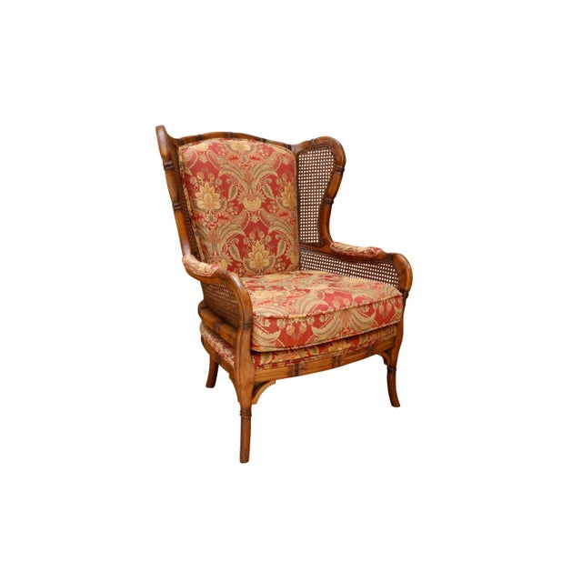 A pair of faux bamboo carved wingbacks with caned sides. Frames are carved throughout to give the look of bamboo nodules,...