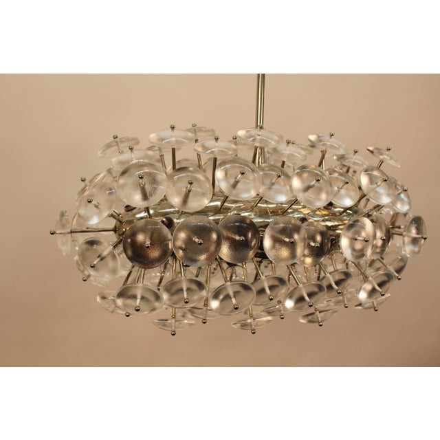 Custom-made Sputnik chandelier composed of thick glass lenses in nickel finish. 32 sockets inserted on main body. Max....