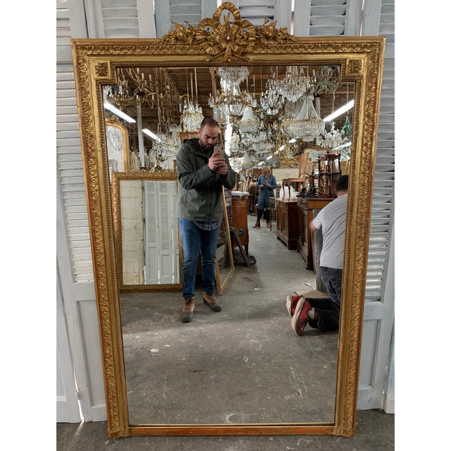 Stunning French Napoleon III period mirror with original glass and elaborately carved giltwood frame. The frame maintains...