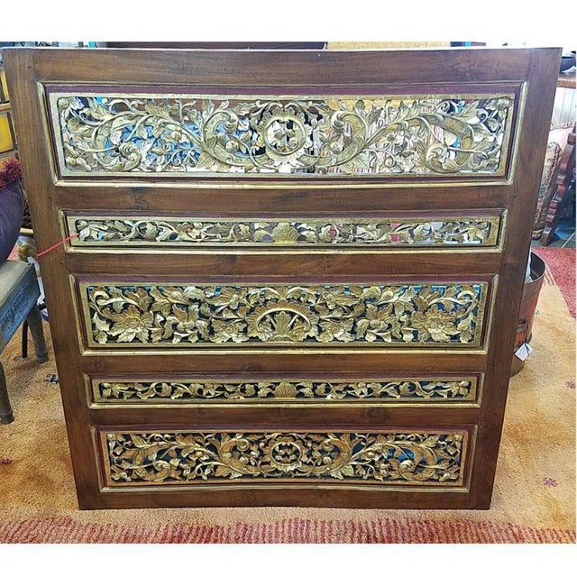 Five Chinese deep relief carved wood panels put together in an elmwood frame. Depicts numerous floral and leafy branches...