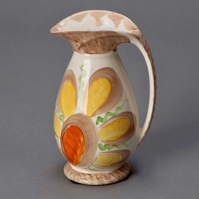 Circa 1920 Myott ceramic pitcher has a flared neck, brown trim and a large yellow and orange flower. Excellent antique...