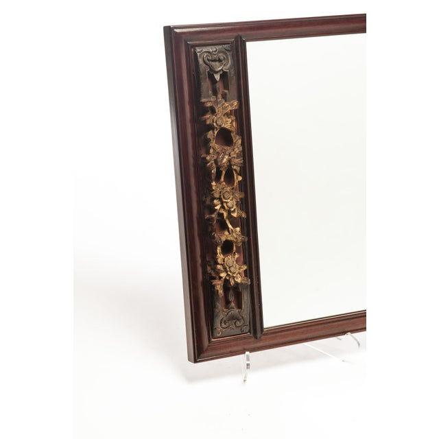 A custom made mirror ca. mid-19th Century decorated with a gilded, hand-carved temple fragment. The temple fragment has...