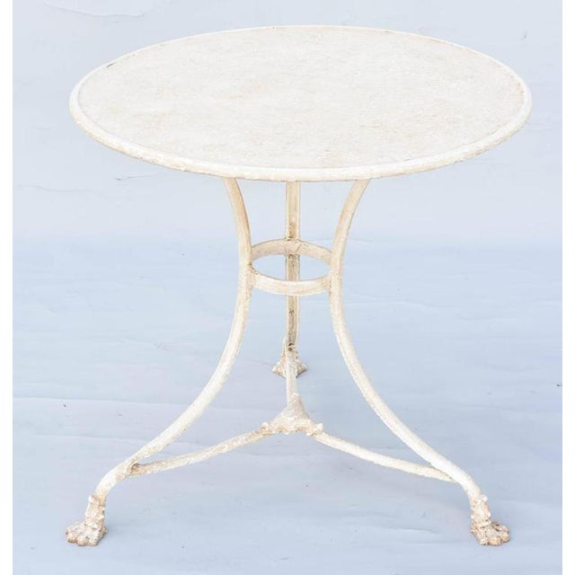 Cafe gueridon table, of painted iron, showing natural wear, its round top raised on three concave and splayed legs, joined...