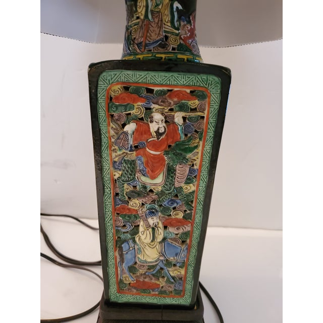 A rare vintage Asian table lamp having impressively detailed ceramic base decorated with figures and dense background in...