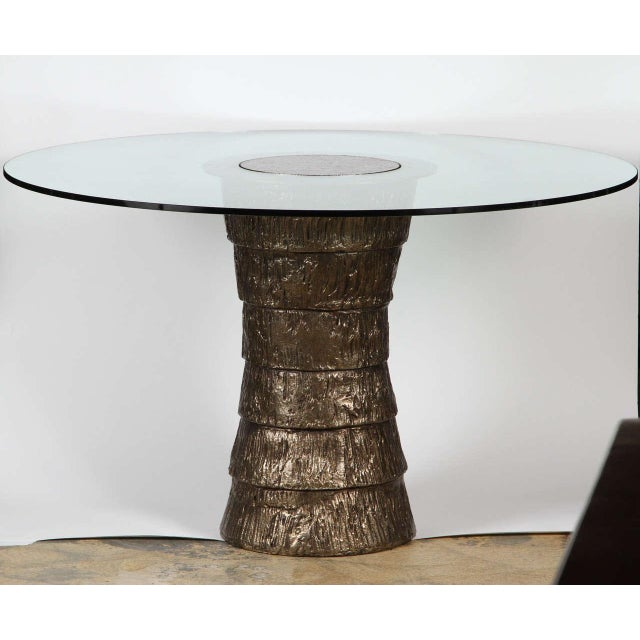 A sculptural steel pedestal style small dining or center table with glass top. Gold textured bronze finish. In the...