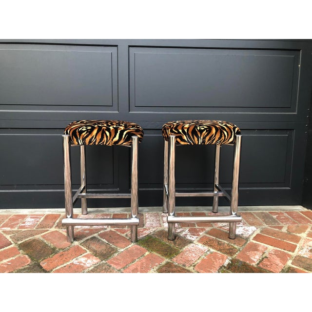 Pair of mid-century chrome stools with cylinder foot rest and funky tiger print velveteen cushions. Groovy! Some wear...