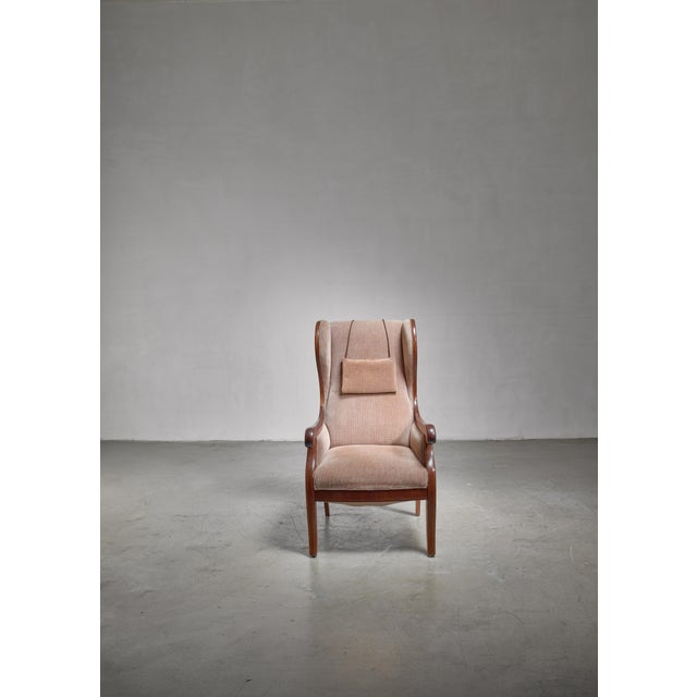 A mahogany wingback lounge chair by Danish designer Frits Henningsen. The chair has scrolled armrests and the original...