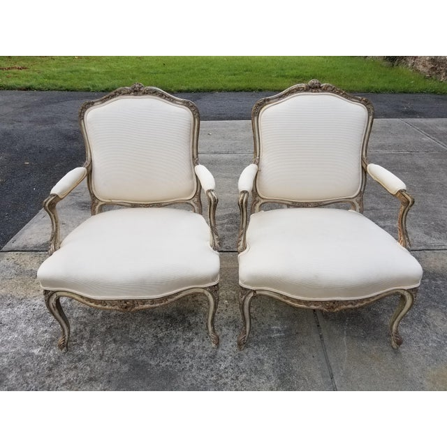 Beautiful pair of French hand carved wood Louis XV style Bergere arm chairs. It is painted in 2 tones of antique white and...